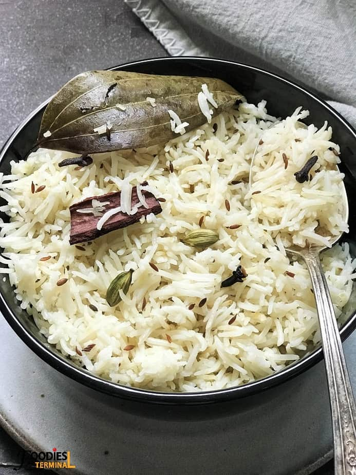 Pressure cooker jeera rice with cumin served in a black bowl with spoon