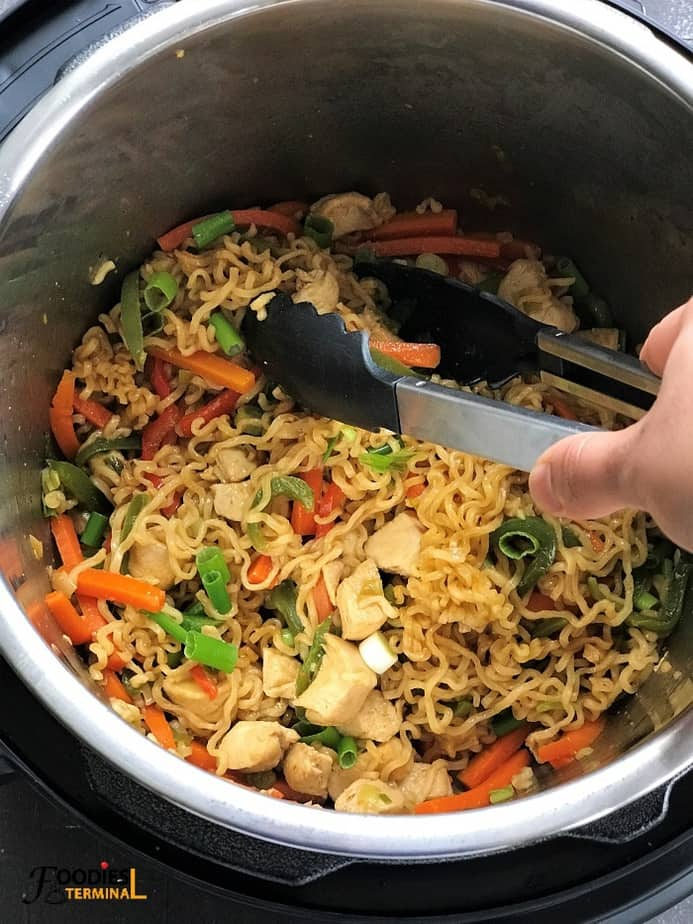 ramen stir fry in instant pot with a black tong