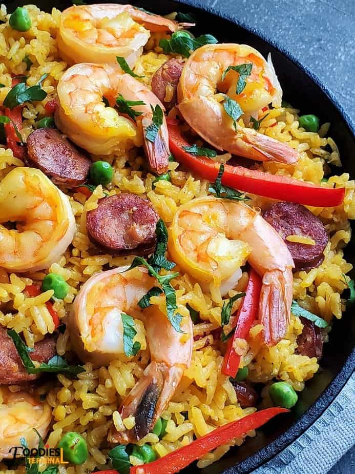 Spanish Paella garnished with fresh parsley with shrimps on top