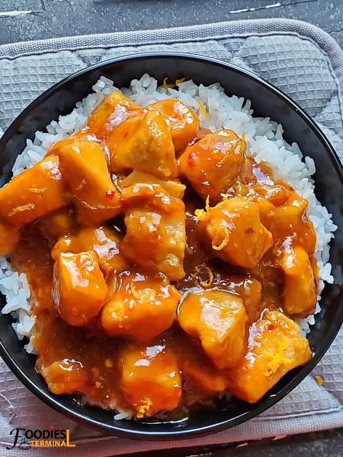 Instant Pot Orange chicken on rice in a black bowl on a grey cloth