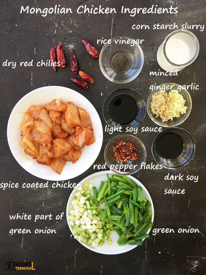 Mongolian chicken ingredients on small bowls on a black surface