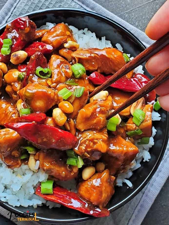 Instant pot kung pao chicken with peanuts on a bed of white rice in a black bowl with chopsticks touching a chicken piece
