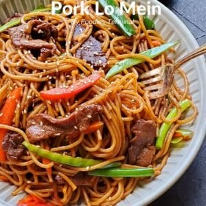 prok lo mein in a off white plate with a silver fork