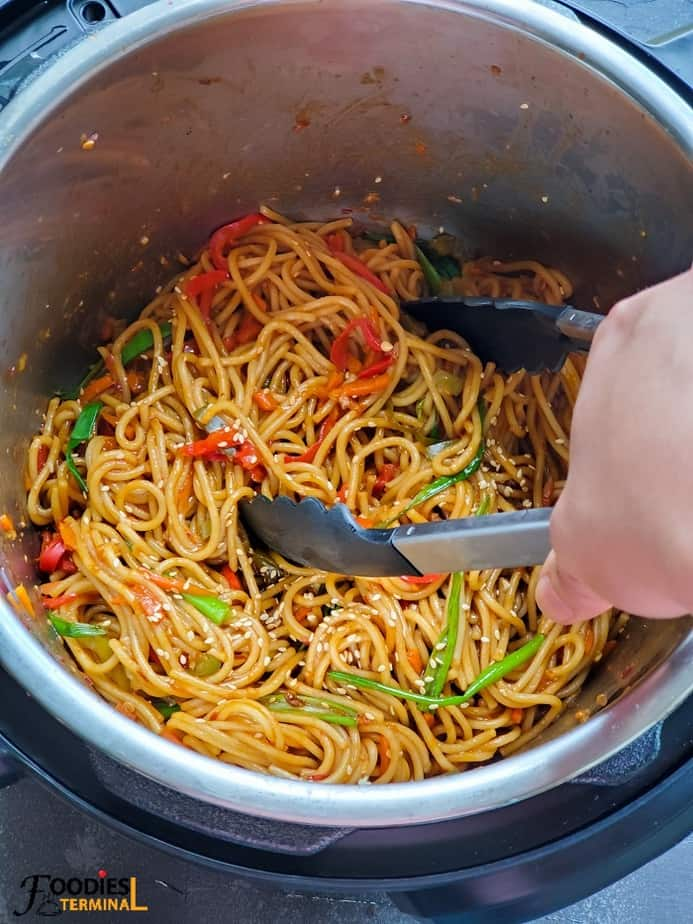 chili garlic noodles in instant pot with a noodle tong