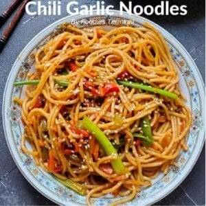 Chili Garlic Noodles garnished with white sesame seeds & served in a white plate
