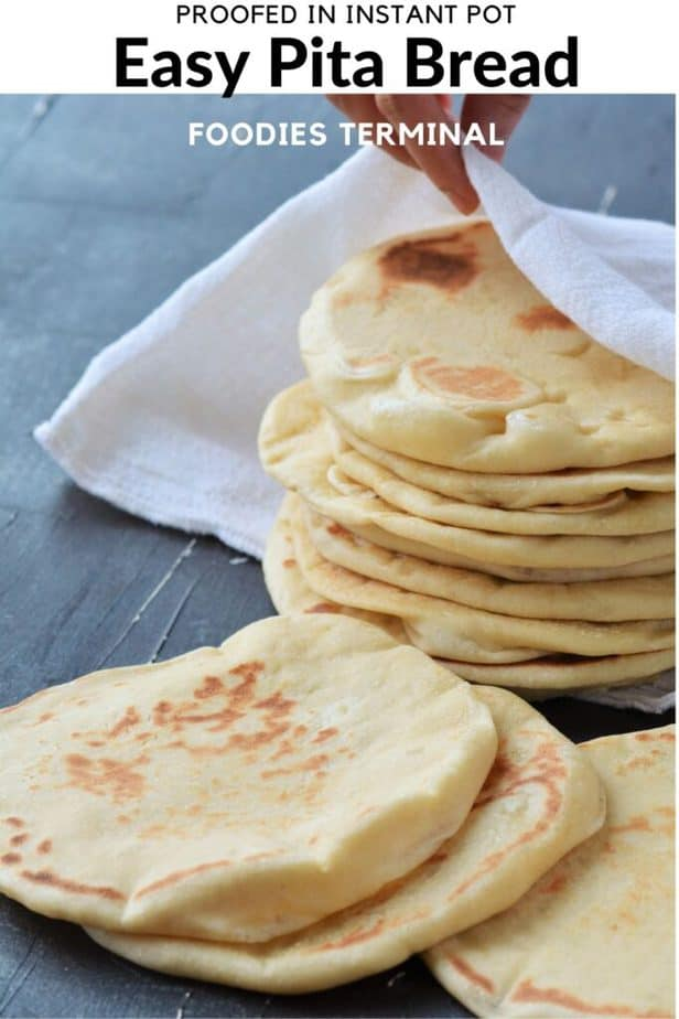 a stack pf homemade pita bread wrapped in a white cloth with three pita pocket bread in front