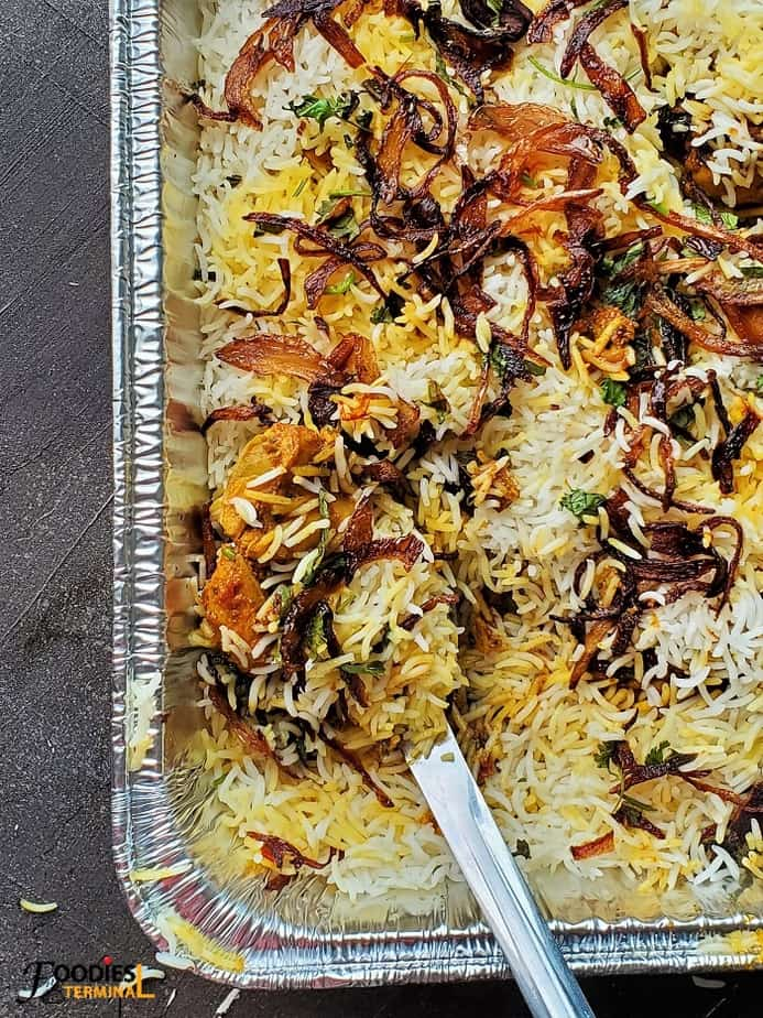 oven baked chicken dum biryani in an aluminum tray with a steel ladle