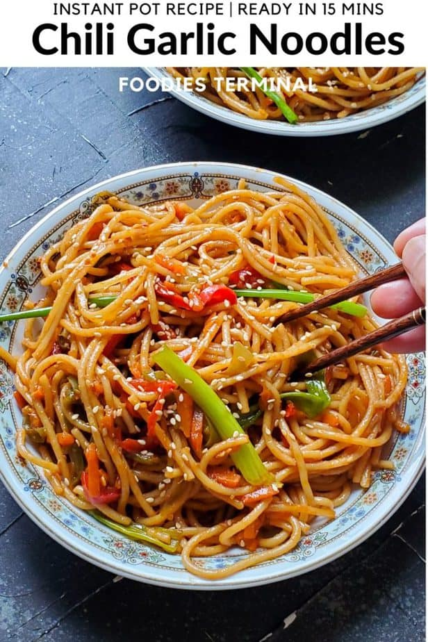 Instant pot chili garlic noodles with chopsticks tucked in served in a white plate