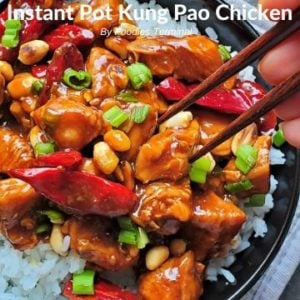 Kung Pao chicken on a bed of rive with chopsticks trying to lift a piece of chicken
