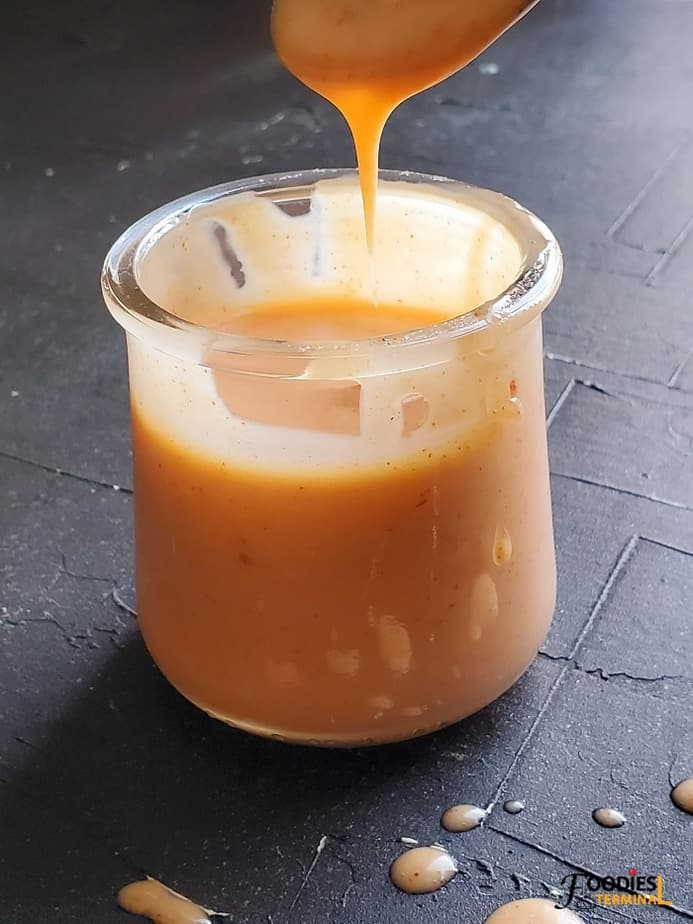 bonefish grill bang bang sauce recipe dripping from a spoon into a small transparent pot kept on a black surface