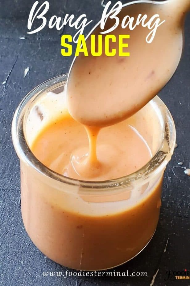 Bang bang sauce with mayo in a glass jar and sauce dripping from a spoon into the jar