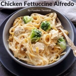 chicken fettuccine alfredo with broccoli in a grey bowl with a fork
