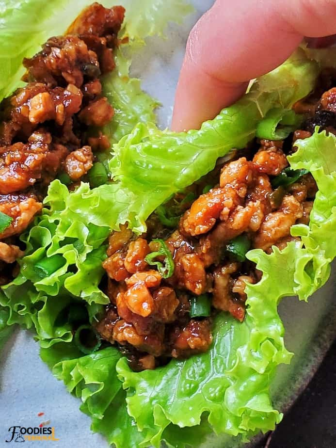 instant pot chicken lettuce wraps being lifted