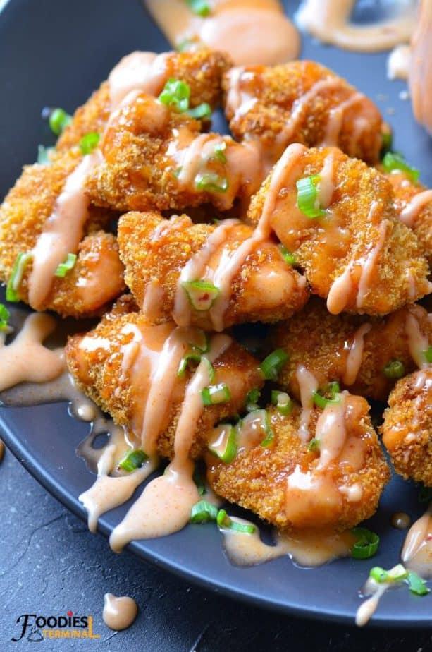 instant pot bang bang chicken drizzled with bang bang sauce on a black plate