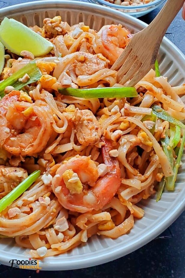 instant pot pad thai with chicken and shrimps in a bowl with a wooden fork