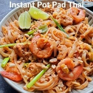 Instant Pot Pad Thai with chicken & shrimp being lifted with a tong