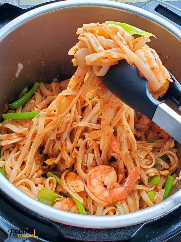 Instant Pot Pad Thai with chicken and shrimps in the instant pot being lifted with tongs