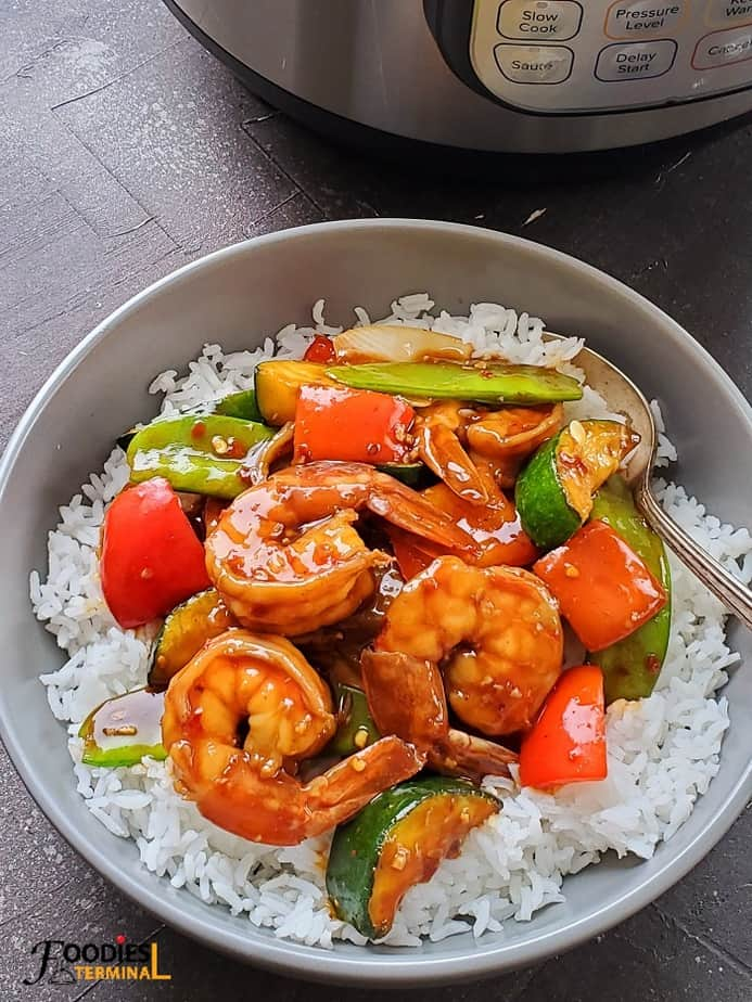 instant pot stir fry shrimp on white rice in a grey bowl with a spoon