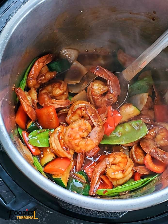 shrimp stir fry recipe in instant pot with veggies and a ladle