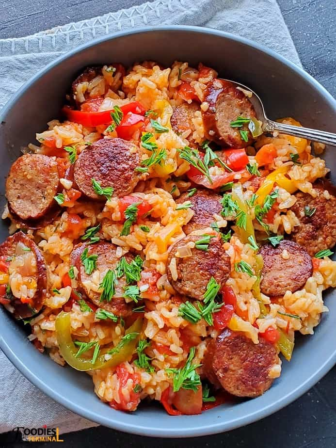 sausage and rice instant pot recipe served in a grey bowl with a silver spoon