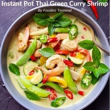 Thai green curry shrimp garnished with thai basil & chilies in a grey bowl