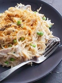 chicken tetrazzini topped with toasted bread crumbs and served in a black plate with a fork on the side