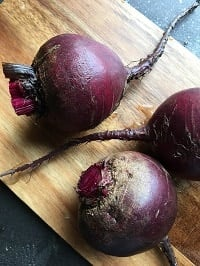 rinsed beets on a wooden chopping board