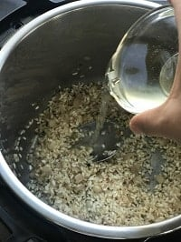 pouring white wine in the pot from a small clear glass bowl