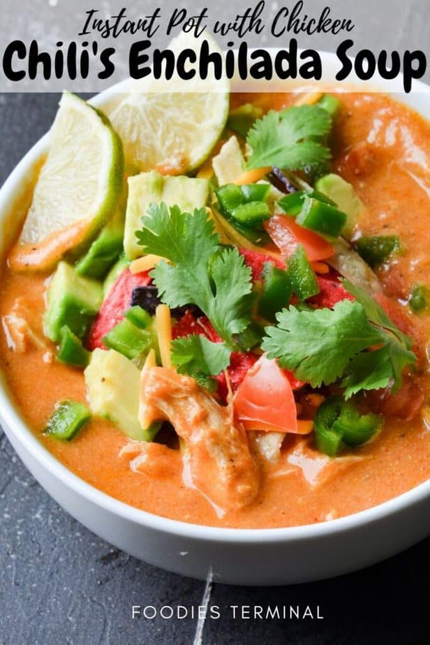 copycat chili's chicken enchilada soup garnished with cilantro, cheese, tomatoes, avocado, jalapeno, tortilla chips, lime in a white bowl