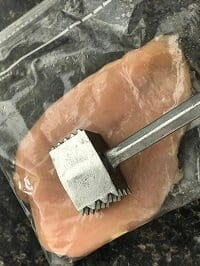 pounding chicken breast inside a ziplock bag