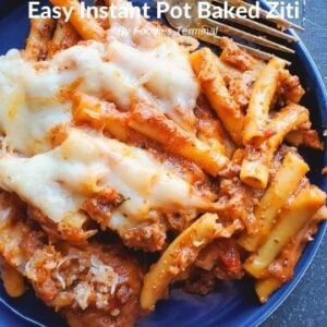 baked ziti on a blue plate with a fork on the side
