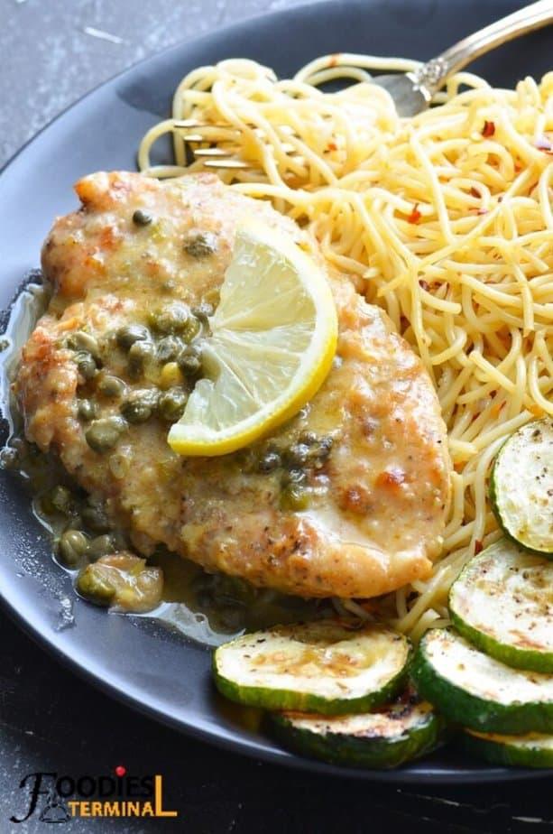 easy chicken piccata on a black plate with piccata sauce & lemon wedge, spaghetti, zucchini