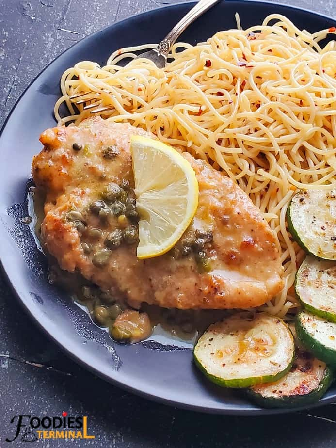 easy chicken piccata served with noodles & zucchini & a lemon wedge on a black plate
