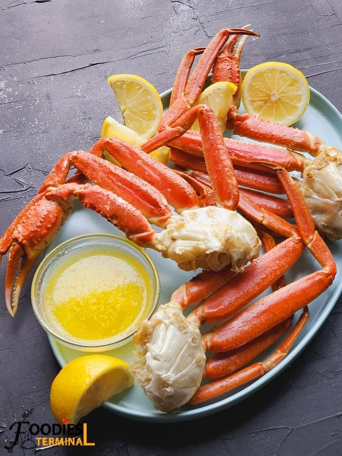 instant pot crab legs served with butter sauce, lemon wedges on a light blue plate