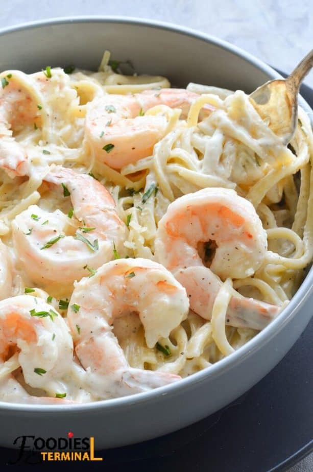best instant pot shrimp alfredo in a grey bowl being lifted with a fork