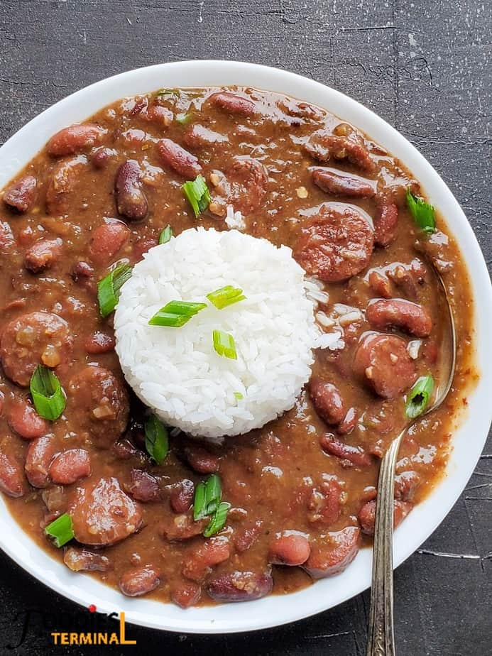 Louisiana style red beans and rice with andouille sausage in a white bowl garnished with scallions