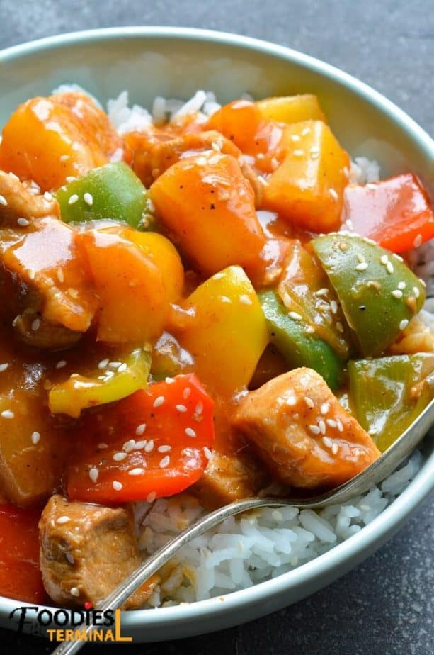 instant pot sweet and sour pork with pineapple over white rice in a bowl with a spoon