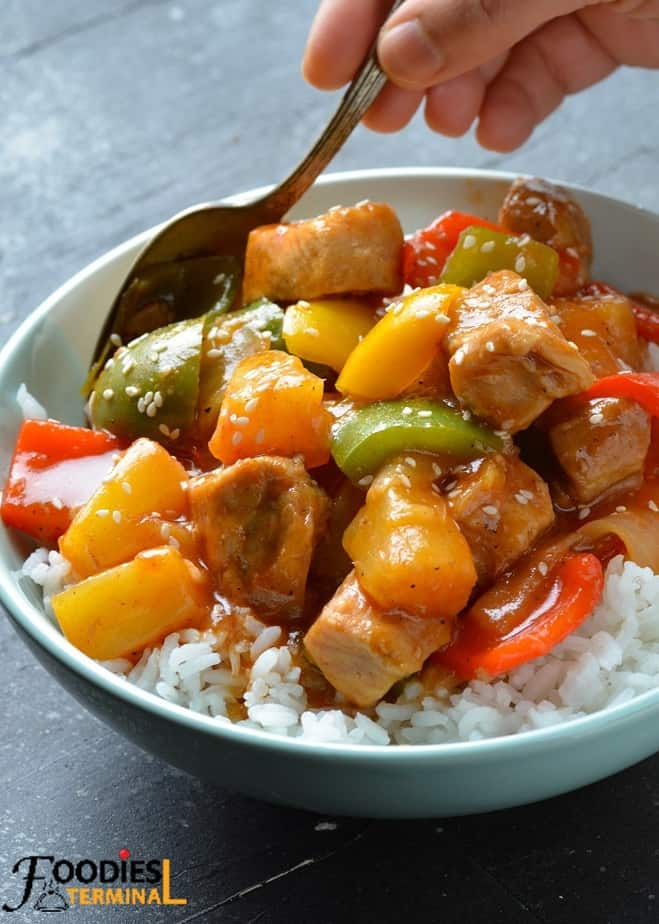 instant pot sweet and sour pork served over rice in a blue bowl with a spoon