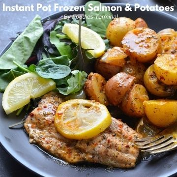 pressure cooked frozen salmon and potatoes served with salad leaves and lemon wedges on a black plate
