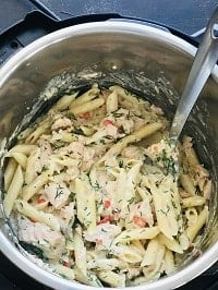 creamy salmon pasta in instant pot with a steel ladle