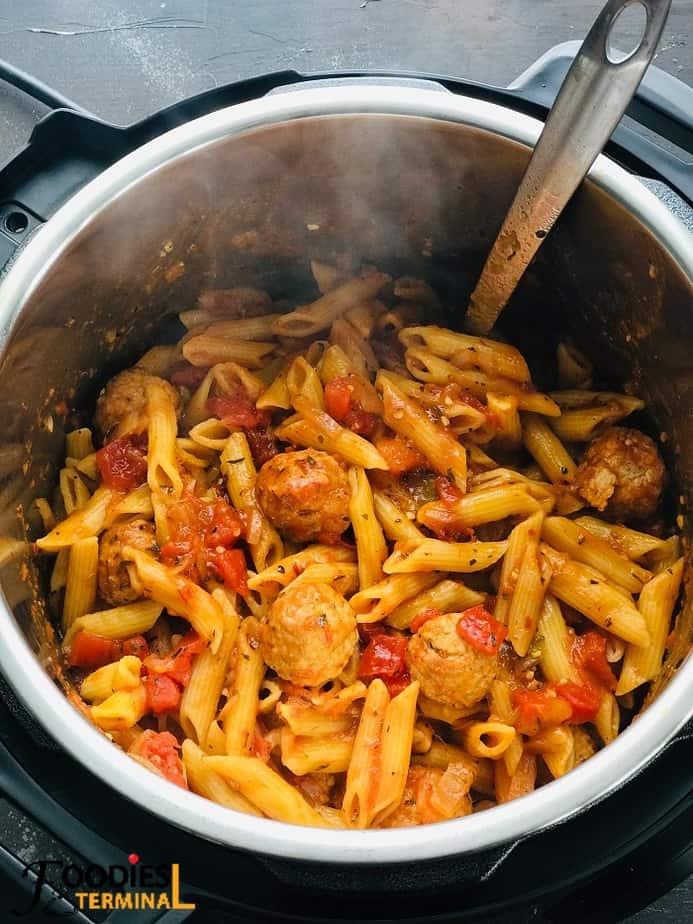 Penne Pasta und gefrorene Fleischbällchen im Instant-Topf mit einer Stahlkelle