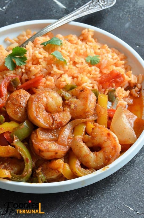 chili's shrimp fajitas made in instant pot served along with mexican rice in a white plate with a silver spoon