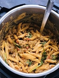 creamy sausage and pasta in instant pot with a steel ladle