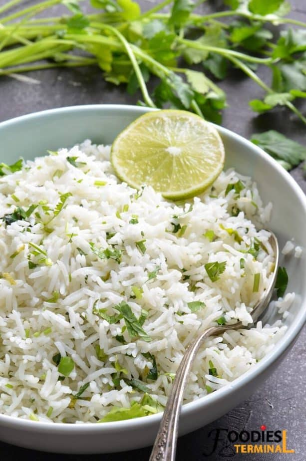 instant pot cilantro lime rice chipotle copycat in a light blue bowl with spoon and lime