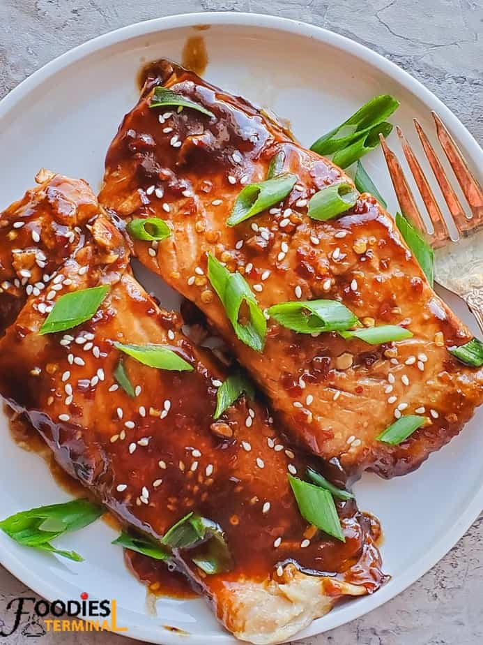 instant pot teriyaki salmon in a white plate garnished with white sesame seeds & green onion