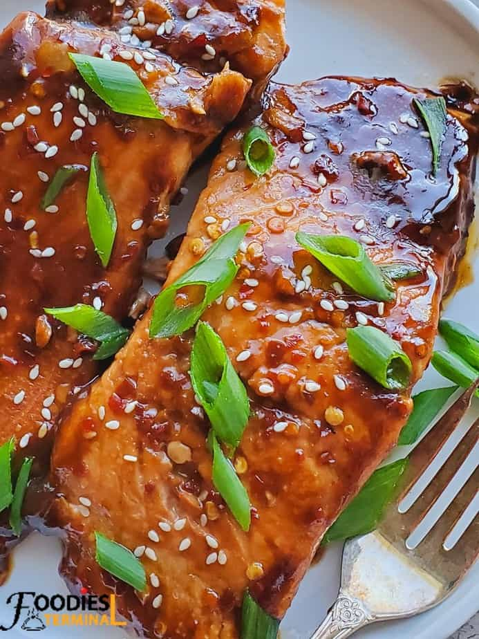 teriyaki salmon fillets garnished with white sesame seeds and chopped scallions