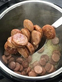 browned sausage in a ladle