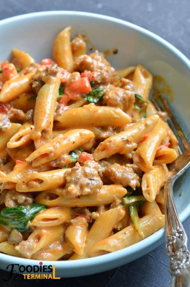 instant pot italian sausage pasta in a light blue bowl with a fork