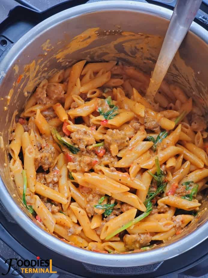 best creamy sausage pasta in instant pot with a steel ladle