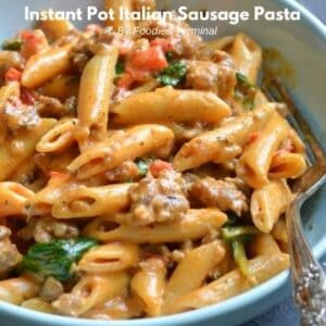 creamy italian sausage pasta in a light blue bowl with a fork
